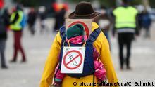 Демонстрант с ребенкои и плакатом против вакцинации