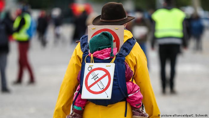 A man carrying a small child on his back, with an anti-vaccine sign