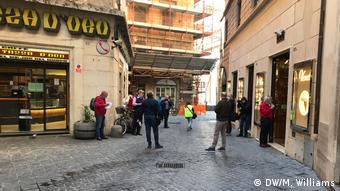 Pessoas em pé diante de lojas num beco de pedestres (DW/M. Williams)