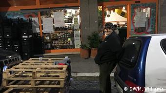 Homem de gorro encostado num carro diante de uma loja e de paletas empilhadas