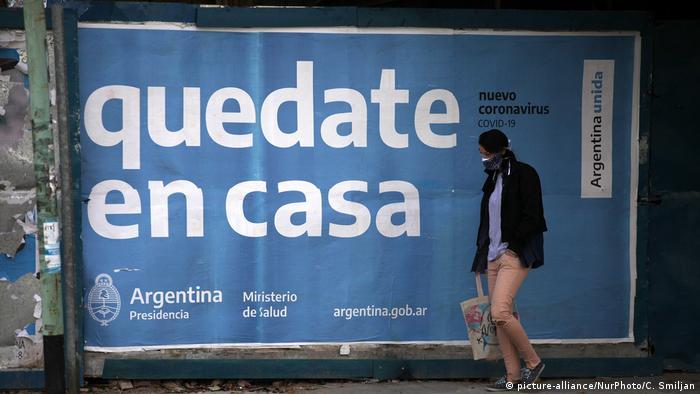 Hombre paseando con mascarilla ante un cartel que pone quedate en casa.