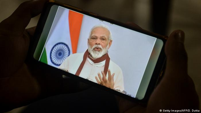 A youth watches Indian Prime Minister Narendra Modi's address to the nation on his mobile phone