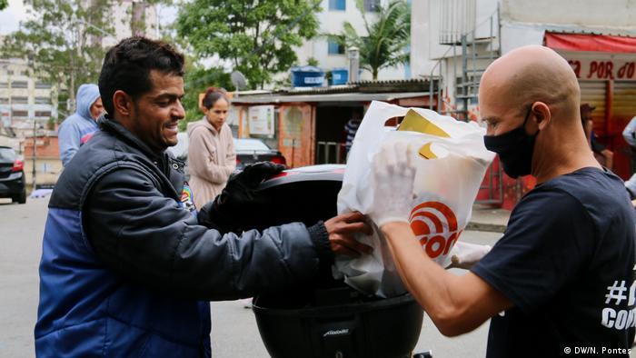 Homem de máscara passando sacola a outro homem na rua