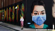 A woman walks past a mural depicting a nurse wearing a protective mask in Shoreditch, amid the coronavirus disease (COVID-19) outbreak, in London, Britain April 21, 2020. REUTERS/Henry Nicholls