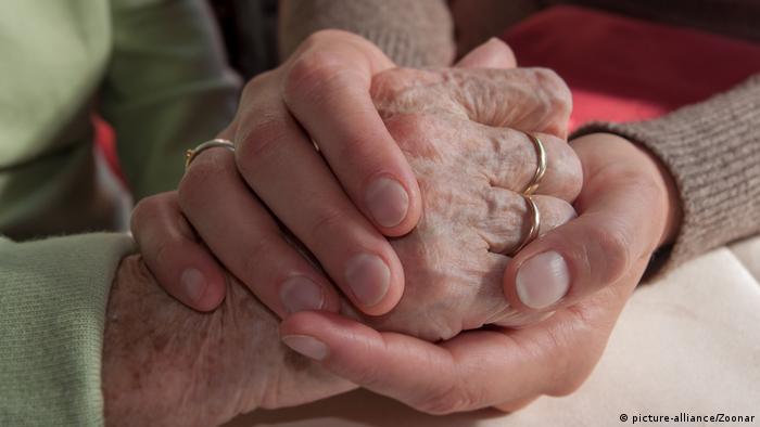 Mão de mulher jovem segura mão de idosa