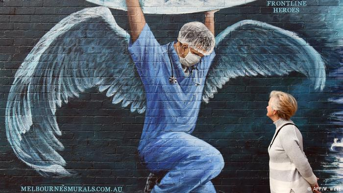 A male nurse is depicted on the side of a building wearing angel-like wings.