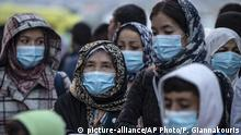 4.5.2020, Piraeus, Griechenland, Refugees and migrants wearing masks to prevent the spread of the new coronavirus, wait to get on a bus after their arrival at the port of Piraeus, near Athens, Monday, May 4, 2020. Greek authorities are moving 400 migrants, mostly families, to the mainland to help ease overcrowded conditions at the camp Moria in Lesbos island. (AP Photo/Petros Giannakouris) |