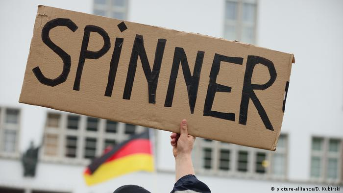 A person at a COVID protest holds a sign reading Spinner, the German for whacko
