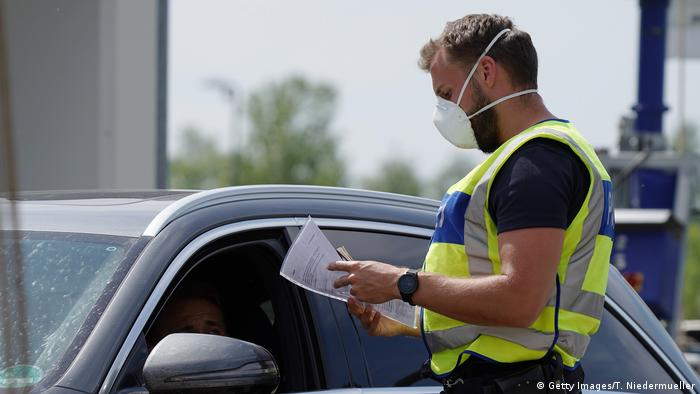 A German border police officers checks the documentation of a driver at a checkpoint