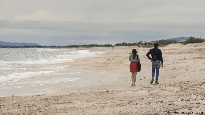 Two people walking on a French beach (Imago Images/H. Lucas)