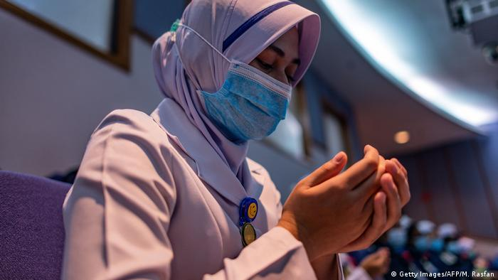Seorang perempuan mengenakan masker dan berdoa (Getty Images/AFP/M. Rasfan)