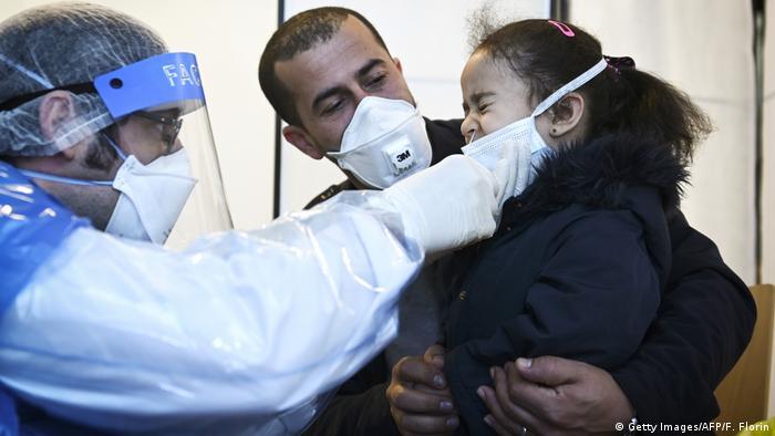 Foto de personal médico francés haciendo un test de coronavirus a una niña
