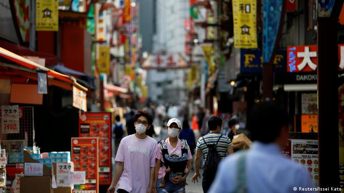 Passersby wearing protective face masks walk on the street as the spread of the coronavirus disease (Reuters/Issei Kato)