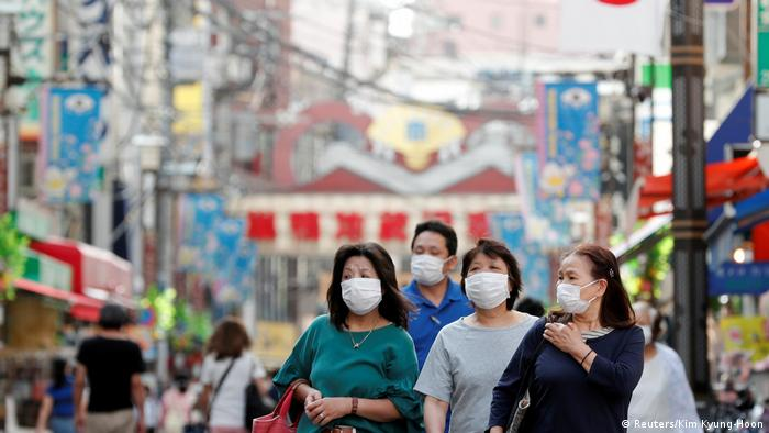 People wearing protective masks make their way at a local market district amid the coronavirus disease