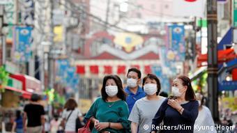Прохожие в масках в столице Японии Токио