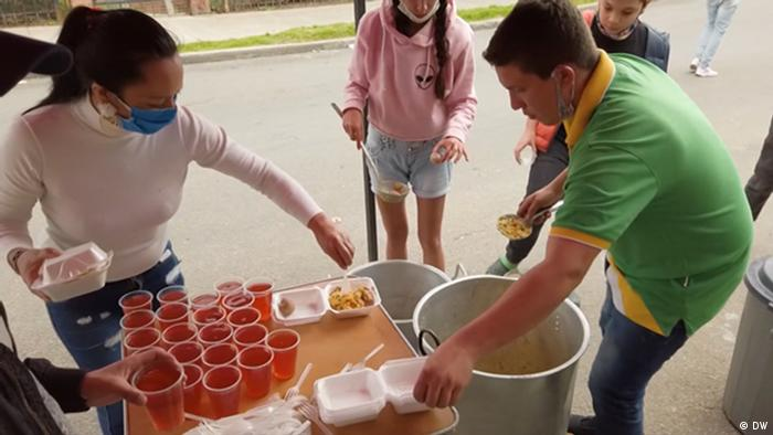 Volunteers dish out food for hungry people