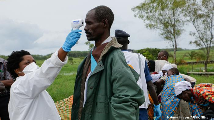 A medical staff member measures a man's temperature