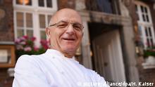 Der Koch Jean-Claude Bourgueil steht am 05.09.2017 in Düsseldorf (Nordrhein-Westfalen) bei einer Pressekonferenz zum 40-jährige Bestehen seines Restaurants Im Schiffchen vor dem Restaurant. Es ist eines der drei Zwei-Sterne-Restaurants in NRW. Foto: Henning Kaiser/dpa | Verwendung weltweit