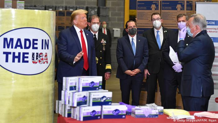 Of six people pictured, only US President Donald Trump does not wear a mask at a mask-making factory (Getty Images/AFP/M. Ngan)