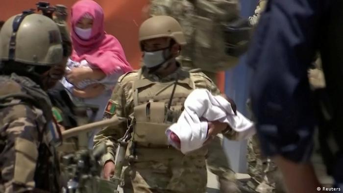Afghan security personnel evacuate a baby from a hospital, where the international humanitarian organisation Doctors Without Borders runs a maternity clinic, that was attacked in Kabul
