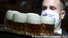 dpatopbilder - 14.05.2020, Österreich, Wien: Ein Kellner mit Mundschutz trägt Bier auf einem Serviertablett durch ein Restaurant. In Österreich könnten ab dem 15. Mai Restaurants unter Einhaltung bestimmter Vorschriften angesichts der Corona-Pandemie wieder öffnen. Foto: Ronald Zak/AP/dpa +++ dpa-Bildfunk +++ |