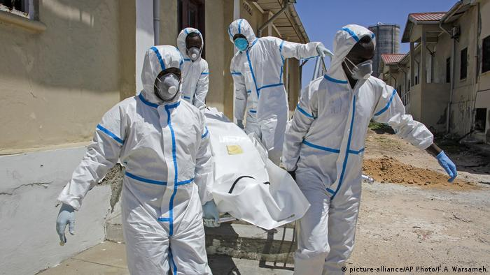 Medical workers in protective suits carry a dead body