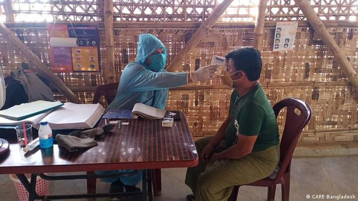 Homem com roupa de proteção azul e máscara coloca termômetro na testa de rapaz