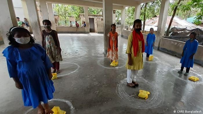 Meninas com roupa colorida em pé sobre círculos de giz desenhados no chão