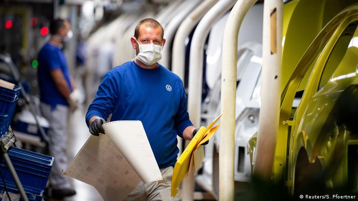 Workers wear protective masks at the Volkswagen assembly line