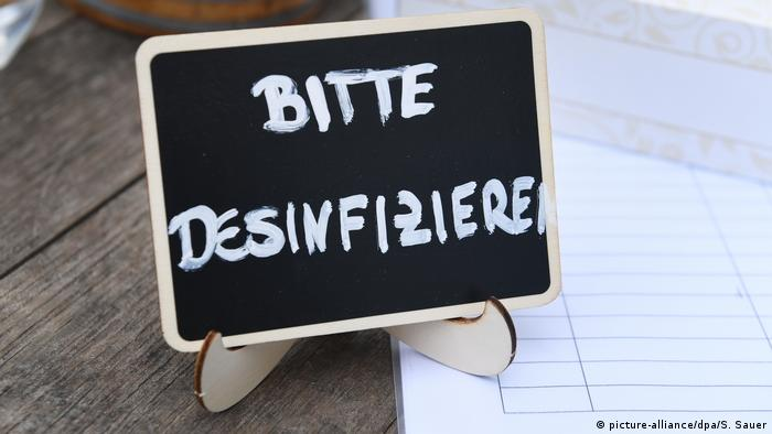 "A sign on a table at a German restaurant says ""Please disinfect""."