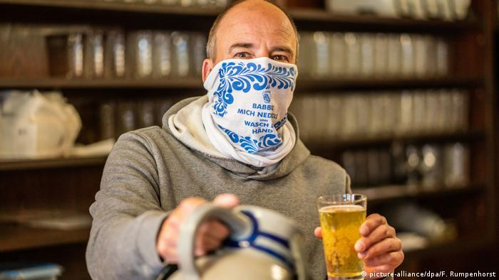 A man with a scarf around his mouth serves apple wine at a restaurant locale in Frankfurt, Germany