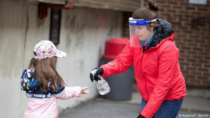 A student has her hands sanitized in a schoolyard in Montreal