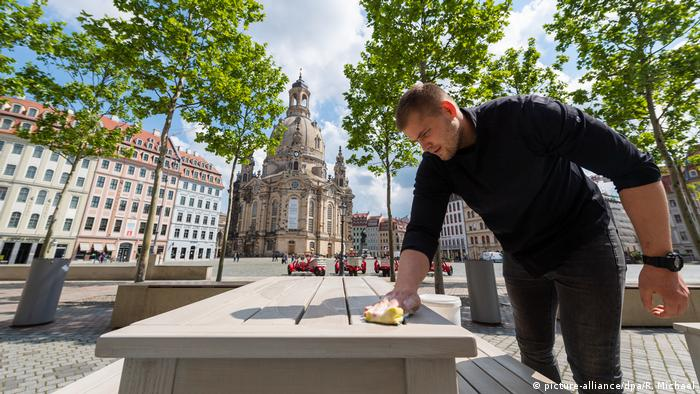 A man wipes down a street-side table outside a restaurant in Leipzig