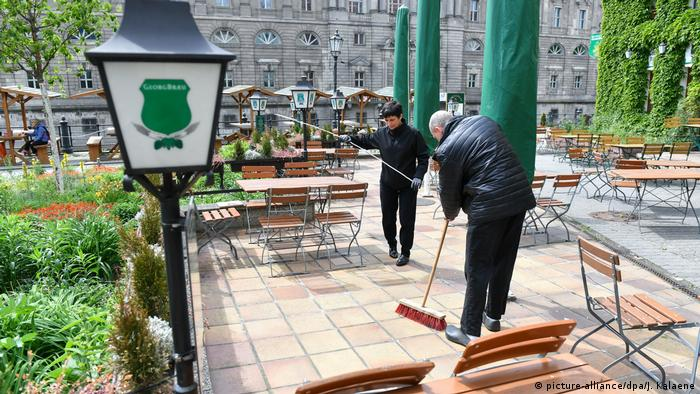 Two people sweep the outdoor patio of a restaurant in Berlin