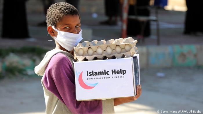 Jemen | Kind mit Mundschutz trägt Hilfsgüter in Taez