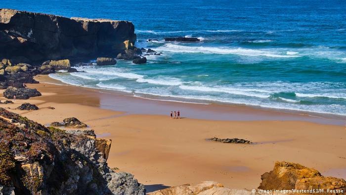 Portugal, people walking on an empty beach at Alentejo Vila Nova de Milfontes