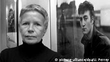 ARCHIV - 06.10.2000, Schleswig-Holstein, Itzehoe: Die Fotografin Astrid Kirchherr steht in der Fotoausstellung über den Musiker John Lennon vor einem ihrer Bilder. Sie starb am Dienstag (12.05.2020) nach kurzer schwerer Krankheit im Alter von 81 Jahren, wie ein enger Vertrauter der Künstlerin am Freitag sagte. Foto: Ulrich Perrey/dpa +++ dpa-Bildfunk +++ | Verwendung weltweit