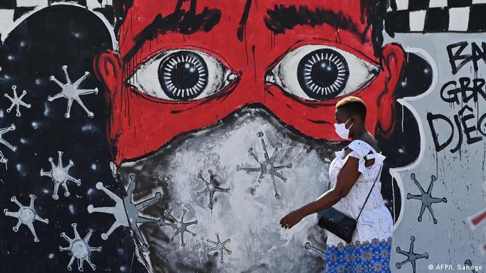 Una mujer de Costa de Marfil pasa frente a un muro grafiteado.