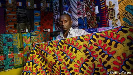 A man holds a traditional Ivorian wax print fabric