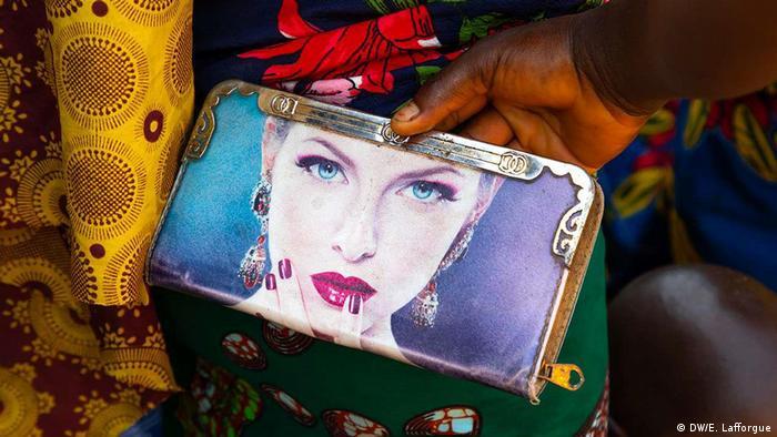 Carteira usada por mulher na Costa do Marfim mostra o rosto de uma modelo bramca