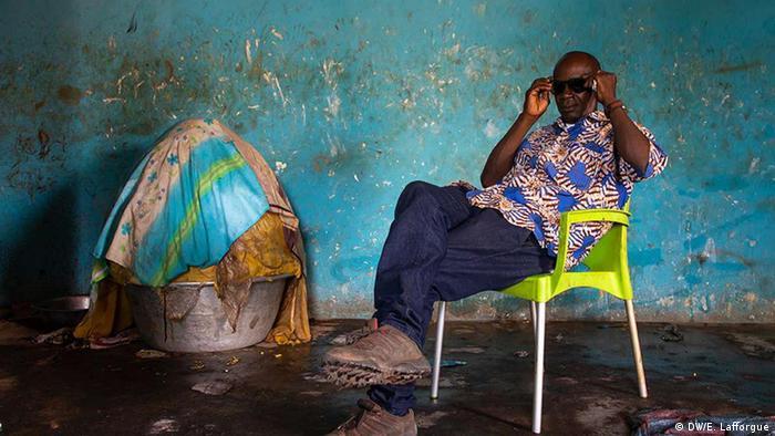 Homem da Costa do Marfim aguarda para comprar manteiga de karité