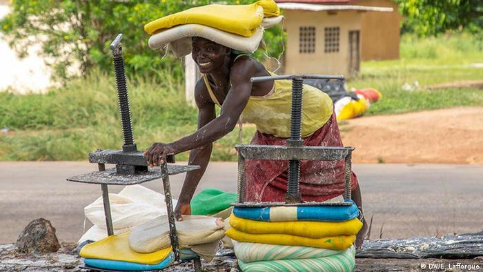 An Ivorian woman from the Femmes battantes cooperative (Women fighters cooperative) wrapes attieke, traditional couscous, in bags