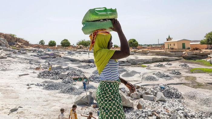 Mulher marfinense trabalha num sítio de mineração