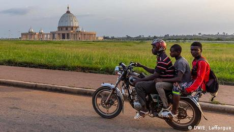 Three young men on a motorbike ride past the Basilica of our Lady of Peace