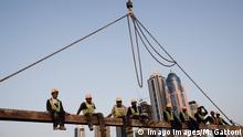 Workers sitting on a crane near a construction site, Dubai, UAE. PUBLICATIONxNOTxINxUAExKSAxQATxLIBxKUWxOMAxBRN Copyright: xMatildexGattoni/arabianEyex MG26269