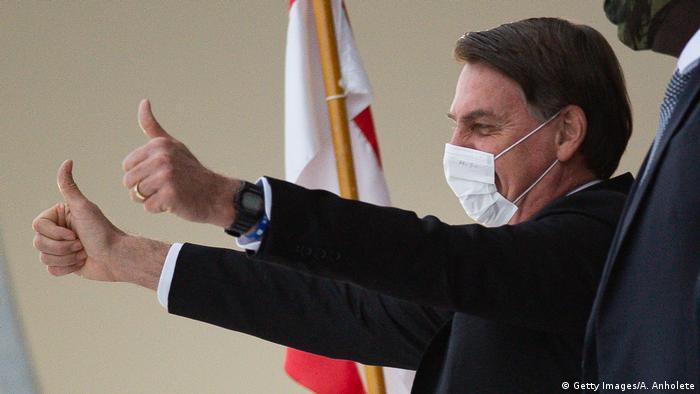 Presidente Jair Bolsonaro faz sinal de ok com as duas mãos usando máscara
