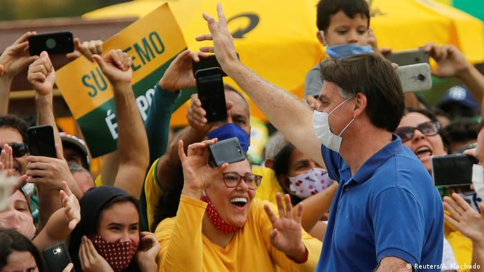 Brazil's President Jair Bolsonaro, wearing a face mask, greets supporters during a protest