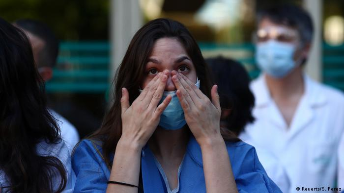 A hospital worker cries while people applaud (Reuerts/S. Perez)
