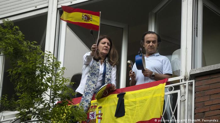 A woman waves a Spanish flag as her partner bangs a saucepan (picture-alliance/AP Photo/M. Fernandez)