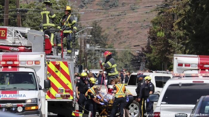 First responders transport an injured person on a stretcher at the scene of the crash